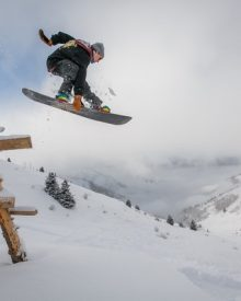 How should a beginner stop on a snowboard?